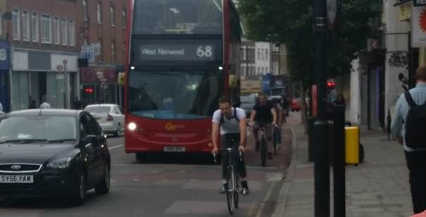 Cyclists squeezing past a bus at Camberwell Green